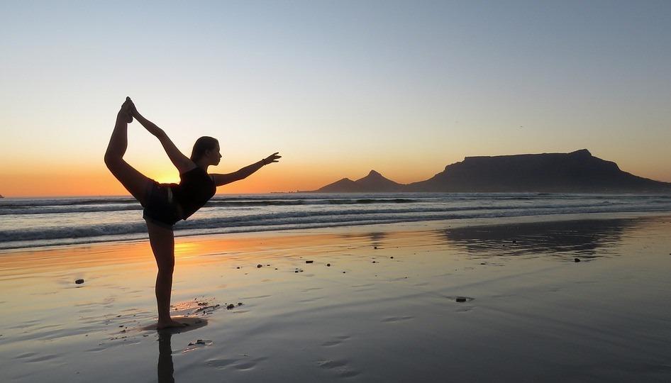 Девушка на пляже занимается йогой